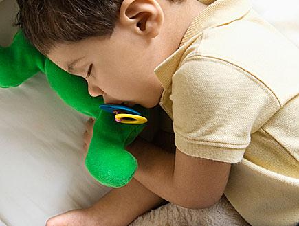 ילד ישן עם מוצץ ובובות (צילום: Creatas Images, Istock)